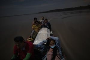 Relatives accompany the coffin that contains the remains of Jose Barbaran who is believed to have died from complications related to coronavirus as they travel by boat on Peru's Ucayali River.