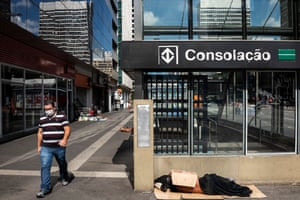 A man wearing a face mask walks past a homeless man sleeping near the entrance of a subway station in the financial district, Paulista Avenue, during the first day of the quarantine in Sao Paulo, Brazil, 24 March.