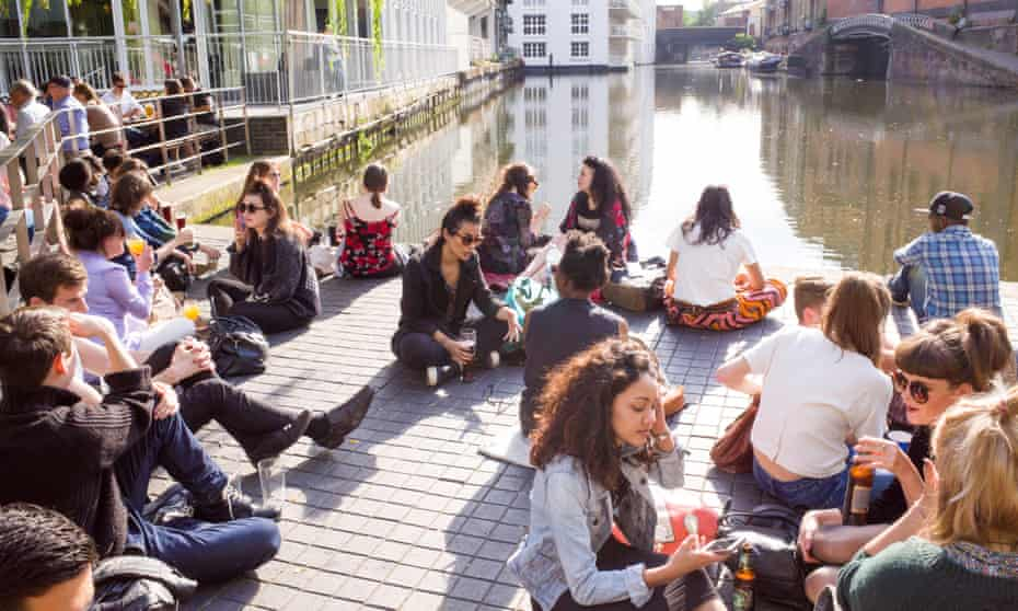 Young people relaxing beside the Regent's Canal in Camden Town, London.