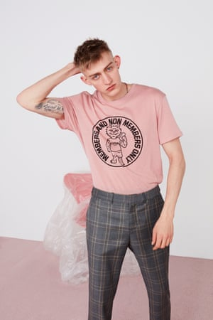 Pink cotton T-Shirt printed with a black motif, grey Prince of Wales wool suit trousers, tide jade, glass and silver necklace