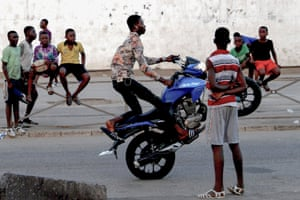 Ivory Coast: a youth performs on a motorbike in the street