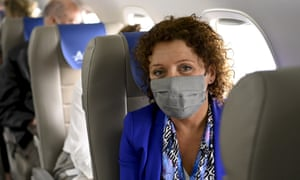 Lydia Peeters in a face mask onboard a plane