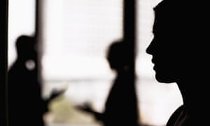 Silhouette of a woman with in an office with coworkers in the background.