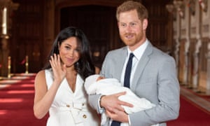 Meghan and Harry pose for a photo with their newborn baby son Archie in St George's Hall at Windsor Castle.