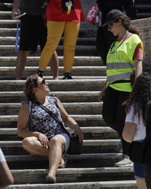 A police officer tells a woman not to sit on the Spanish Steps