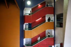 Actors from the Mystorin Theatre Ensemble, and a passerby, walk down the stairs during the group's show Seven, a site-specific act that uses all seven floors of the bus station