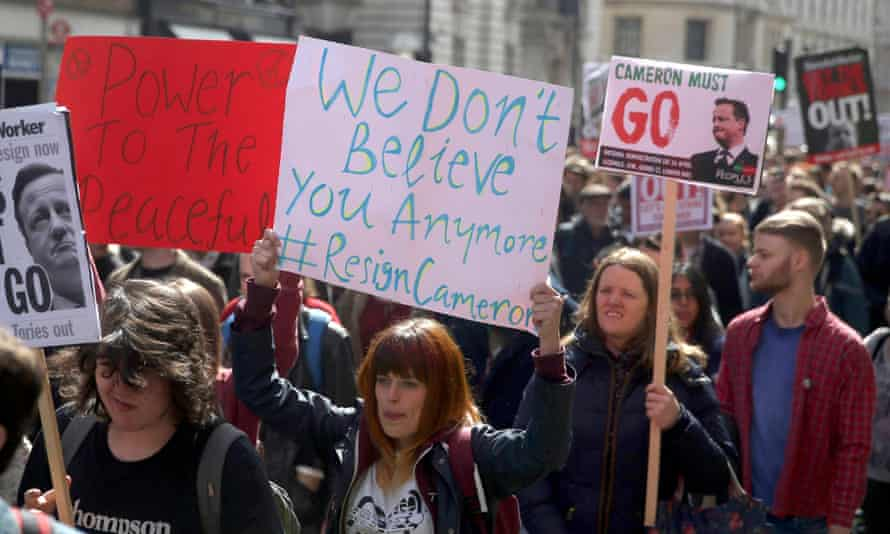 Demonstrators hold placards during a protest in Whitehall