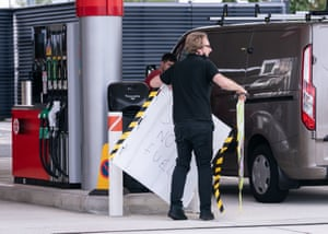 An employee removes a no fuel sign from the forecourt of a petrol station in Leeds today
