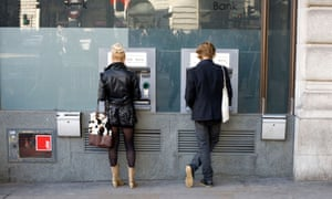 People withdrawing cash from a bank dispenser