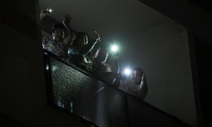 People light their smart phones on a balcony as part of nationwide flash mob to light up Italy