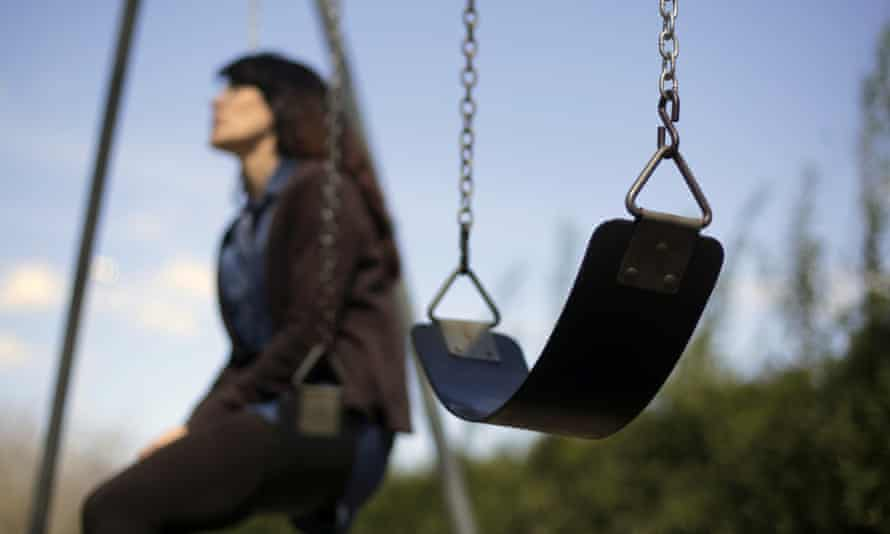 Woman sits alone on a swing with an empty one beside her