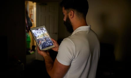 Ahmed (not his real name) at home in Lancaster looking at photographs of a fire at the refugee camp at Samos, a Greek island.