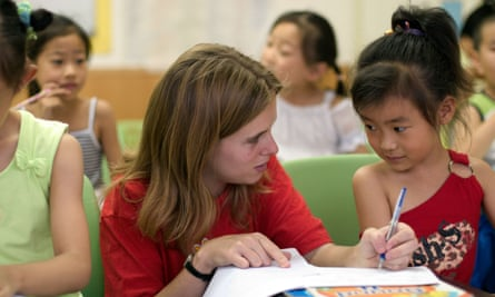 Western woman teaching English to a Chinese girl