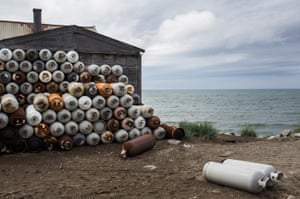 Used propane tanks sit outside a house on the beach.