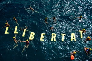 People swim in the sea around floating letters forming the word 'freedom' in Catalan during a pro-independence gathering in Badalona, Spain