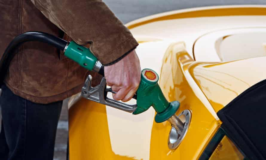 A man uses an unleaded petrol pump