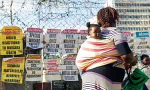 A woman carrying a child walks past newspaper headlines on a street in Harare, 7 September 2019.