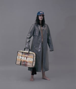 Nassia wears vinyl trenchcoat, £256, and denim briefs, £167, by Ludovic de Saint Sernin, from The Webster. Bag, from a selection, by Marco de Vincenzo. Vintage Arbor Acres cap, stylist's own