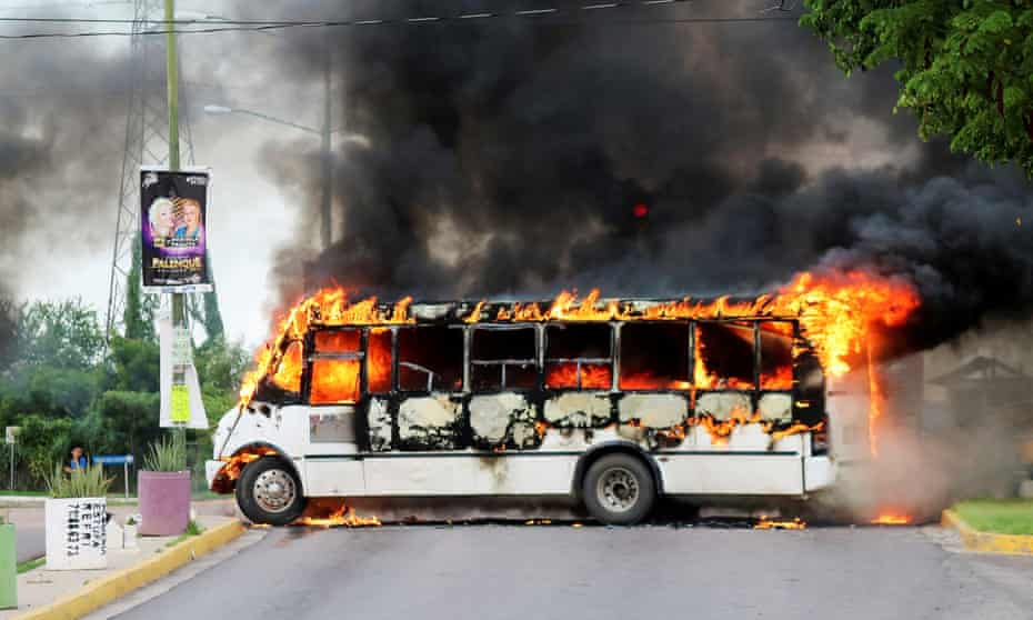 """A burning bus, set alight by cartel gunmen to block a road, is pictured during clashes with federal forces following the detention of Ovidio Guzman, son of drug kingpin Joaquin """"El Chapo"""" Guzman."""