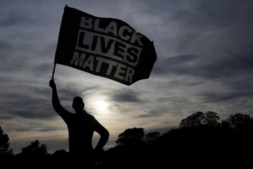 Silhouette of a man waving a large Black Lives Matter flag against a background of the setting sun.