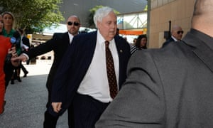 Clive Palmer, flanked by security guards, arrives at the federal court in Brisbane on Monday