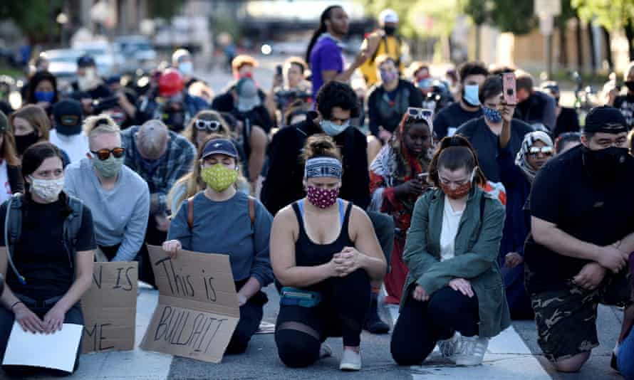 Kneeling protesters in face masks observe a moment of silence in Minneapolis