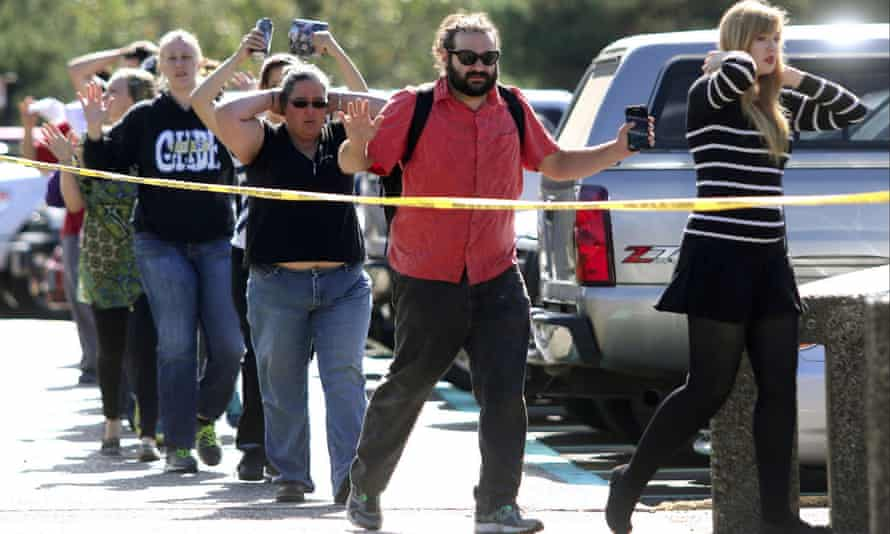 Police search students outside Umpqua Community College in Roseburg, following a deadly shooting at the southwestern Oregon community college.
