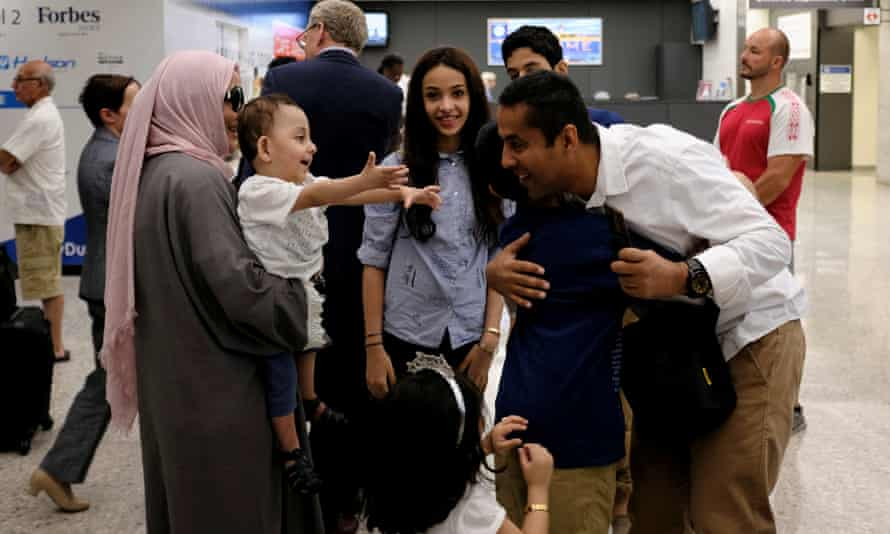 A family embraces each other as members arrive at Washington Dulles international airport after the supreme court granted parts Trump's travel ban into effect on Monday.