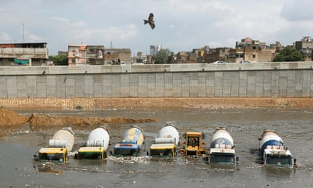 Concrete mixers submerged in flood waters in Pakistan. Profits in the building industry could be affected by higher carbon pricing.