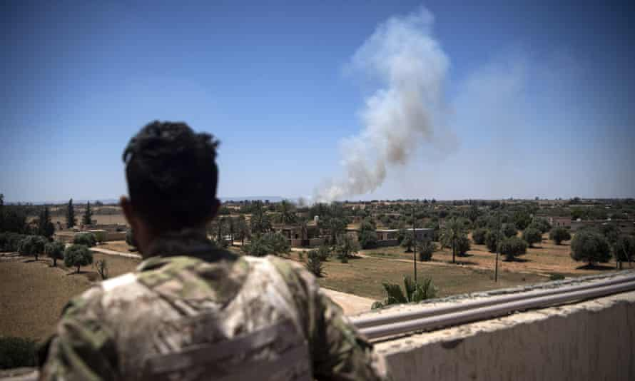 A fighter loyal to the internationally recognised Government of National Accord watches as smoke rises in the distance during clashes with forces loyal to Khalifa Haftar, in Espiaa, about 40km south of Tripoli on 29 April 2019.