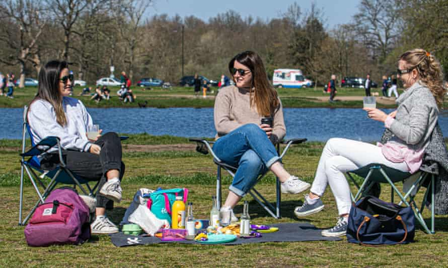three women sitting on chairs having a picnic in a park
