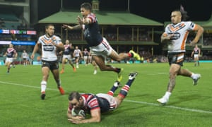 Boyd Cordner of the Roosters scores and Latrell Mitchell of the Roosters leaps in the air against Wests Tigers at the SCG in Sydney.