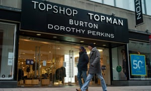 Members of the public walk past a store encompassing Top Shop, Top Man, Burton and Dorothy Perkins in London.