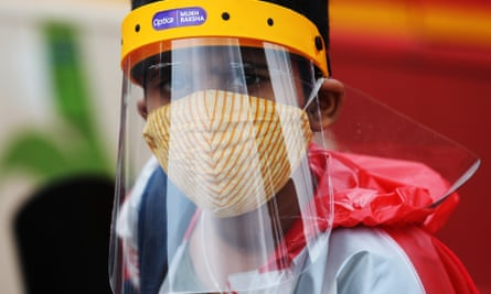 A boy wearing PPE in Bangalore, India, which is going into a one-week lockdown.