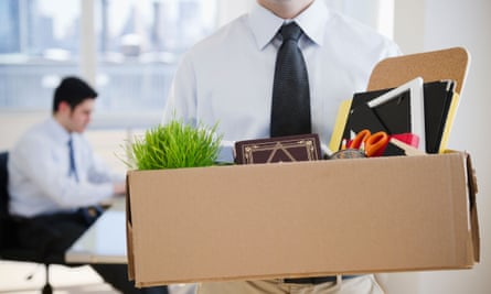 Male office worker carrying personal belongings from the office as if fired