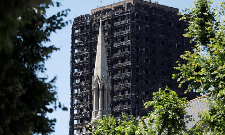 The spire of the Notting Hill Methodist Church stands in front of Grenfell Tower, destroyed in a catastrophic fire