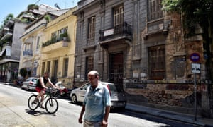 People pass a neoclassical building for sale in one of the oldest districts of Athens.
