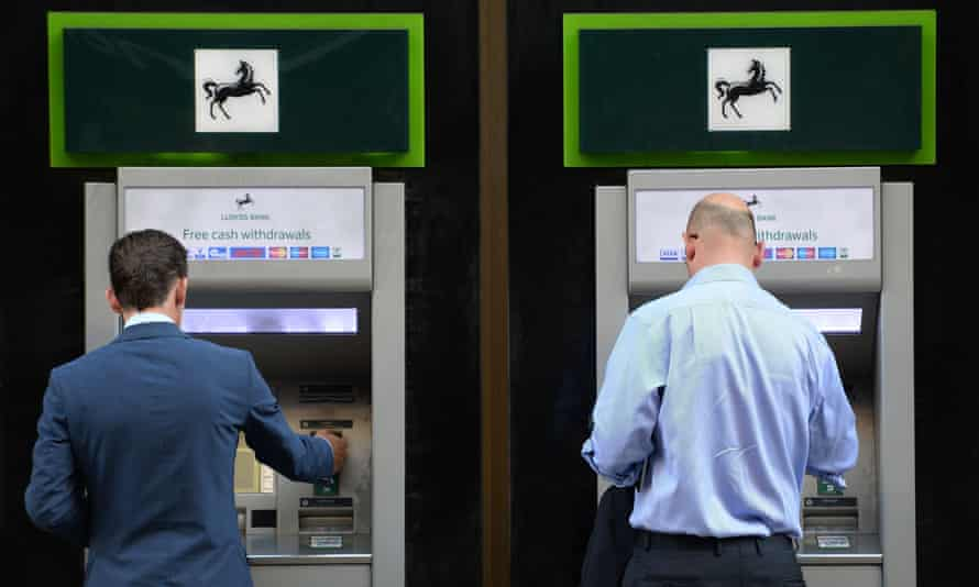 Two men withdraw cash from a Lloyds Cashpoint