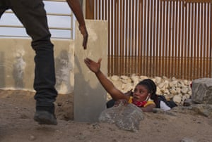 A Haitian migrant family member reaches out for help while emerging from a rocky canal adjacent to a gap in the US border wall in Yuma