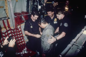 Noriega watches as US drug enforcement agents place chains around his waist on board a C-130 transport plane in 1990