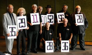 Members of the stolen generation (L-R): Stephen Maher (35), Cecil Bowden (29), Lester Maher (11), Peter Knight (10), Manuel Ebsworth (28), Greg Thompson (52), Michael James Welsh (36), Harry Ritchie-Cook (56) and Richard Campbell (28) pose with their assigned numbers from the Kinchela boys' home in NSW.