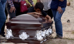 A grandson of the murdered Mexican journalist Carlos Dominguez Rodriguez mourns over his coffin.