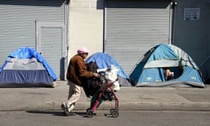 A person walks past tents in Los Angeles, California, on 9 February 2016. Studies have shown that only one in four Americans who need housing assistance actually receive it.