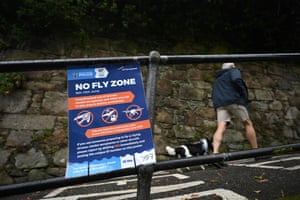A dog walker passes a sign advising of a no-fly zone in St Ives
