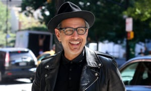 Jeff Goldblum smiling, wearing a biker jacket and trilby