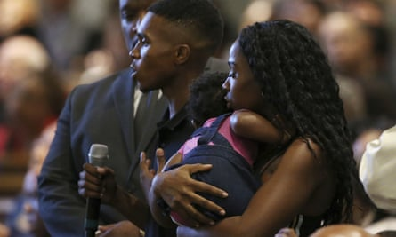 Dravon Ames and fiancée Iesha Harper, with 1-year-old daughter London, at a community meeting about police brutality.