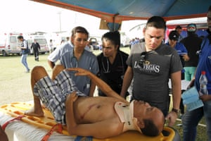 An injured man is attended to at the Maximino Puertas stadium as rescue efforts continue in Pedernales