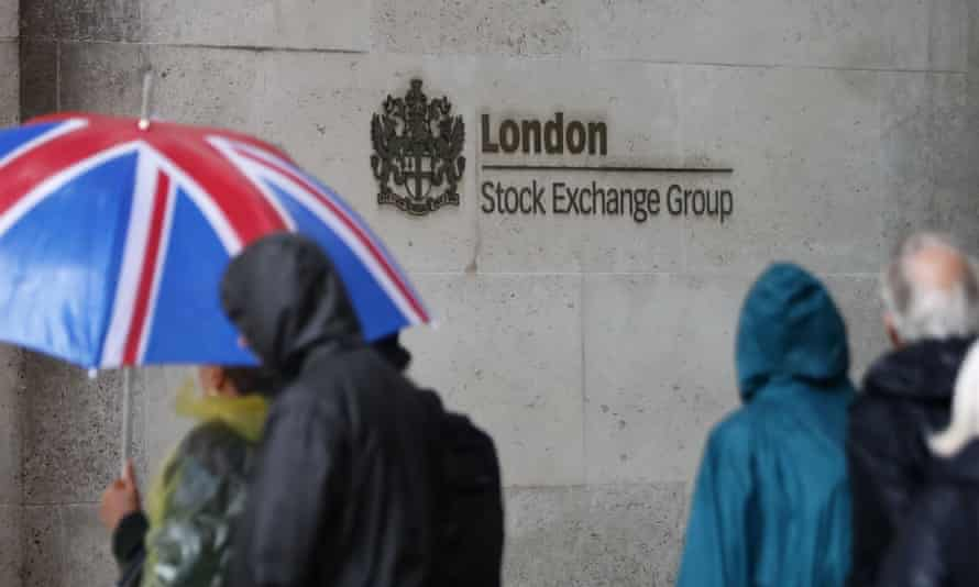 Commuters walk past the London Stock Exchange in the City of London