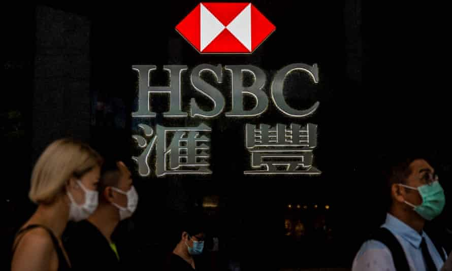 pedestrians walking past the logo for HSBC in Hong Kong