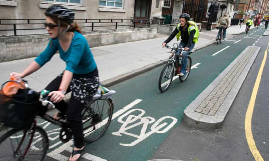 Cyclists riding in segregated cycling lane, London, England, UK